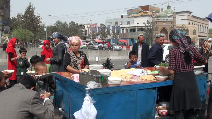 HOTAN - SEPTEMBER 10 2010: Uyghur people are ordering food from a local stand on the streets of Hotan, in China
