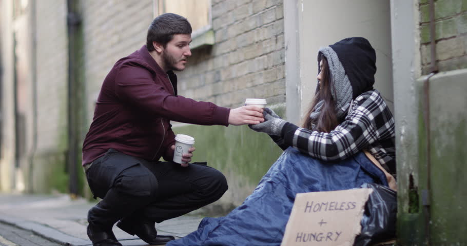 4k, A kind hearted young man offering a cup of coffee to a homeless person sitting outside in cold. Slow motion