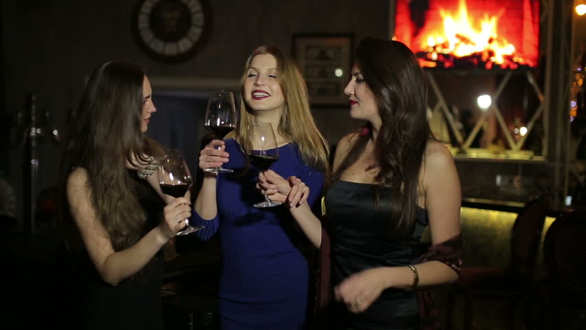 sexy girls relaxing with glass of red wine in night club
