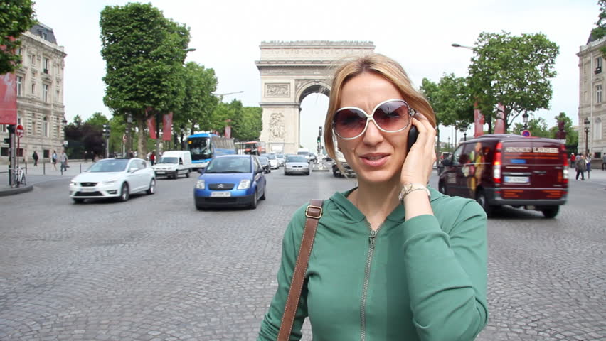 Happy woman talking on a mobile phone on the Champs Elysees street, near the Arc de Triomphe in Paris, France | Shutterstock HD Video #24662444