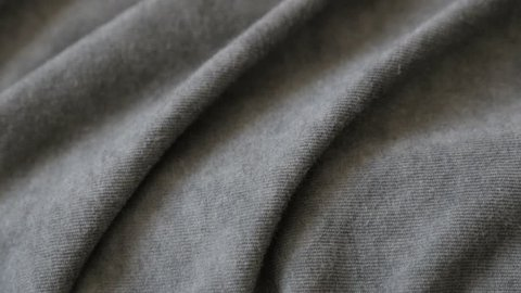 Modern clothing silky gray sample slow tilt 2160p 30fps UltraHD footage - Tilting on dark grey smoked color fine t-shirt fabric close-up 4K 3840X2160 UHD video