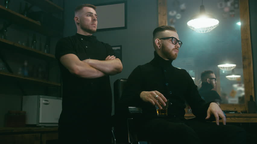 4K CINEMAGRAPH - Young satisfied Caucasian man sitting with whiskey after a getting haircut in a modern barber shop. Seamless loop. 4K UHD Raw edited footage