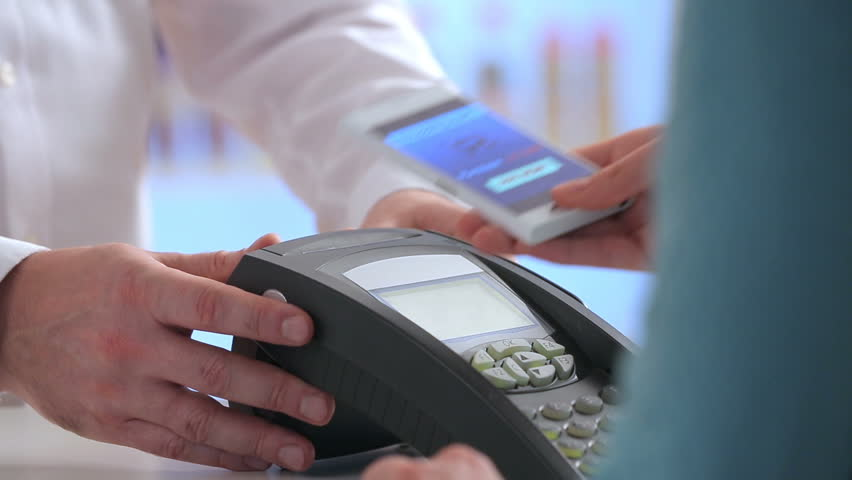 Woman paying through smart phone using NFC technology. Close up. | Shutterstock HD Video #24693959