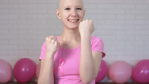 Happy breast cancer survivor woman fighting breast cancer making boxer's punches -breast cancer awareness concept