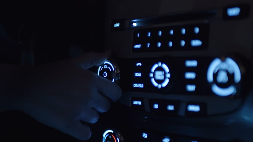 Closeup Of Female Driver's Hand Turning Up Volume On Car Radio At Night