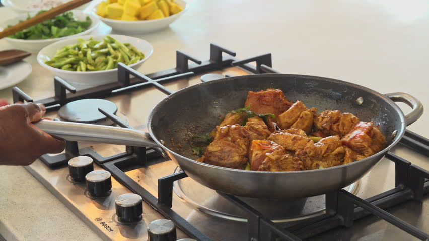 Close up of a frying pan as a chef tosses the pan and stirs a sri lankan chicken curry.