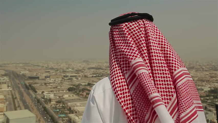 Mid shot of a Saudi Arabian man in local dress standing on a roof looking out across the city of Jeddah, in Saudi Arabia in the Middle East on a windy day. | Shutterstock HD Video #24706343
