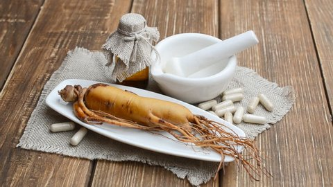 Ginseng root with pharmaceutical bottle, mortar, pestle. Rotate on board.