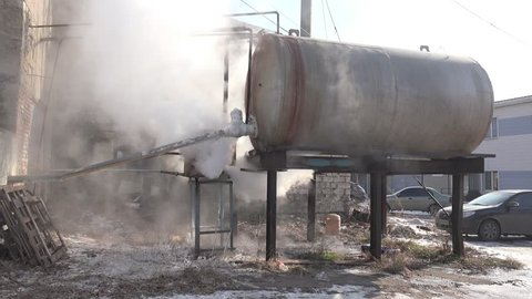Large tank on iron rusty supports emits hot steam to air in an old factory