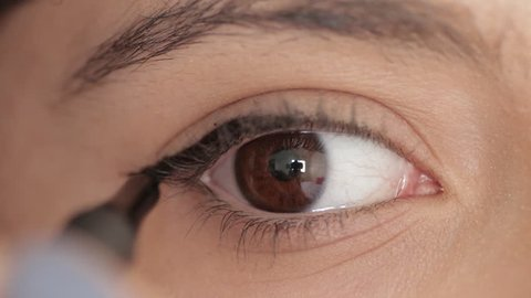 Macro woman apply eyeliner in slow motion