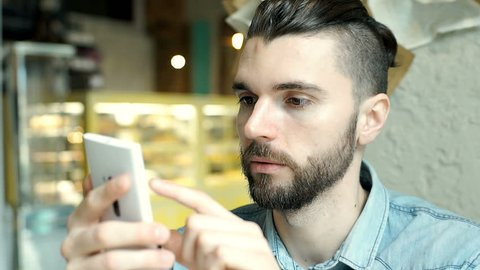 Handsome man with mun bun looks shockes and worried while checking news on smartphone