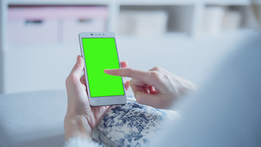 Young Woman sitting on a couch uses SmartPhone with pre-keyed green screen. Few types of motion - scrolling up and down, tapping, zoom in and out. Perfect for screen compositing. 10bit ProRes 444.   Shutterstock HD Video #24787382