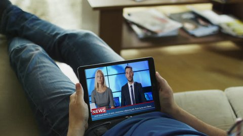 Relaxed Man Lying on His Couch Watches News Broadcast on His Tablet Computer. Shot on RED Epic Cinema Camera in 4K (UHD).