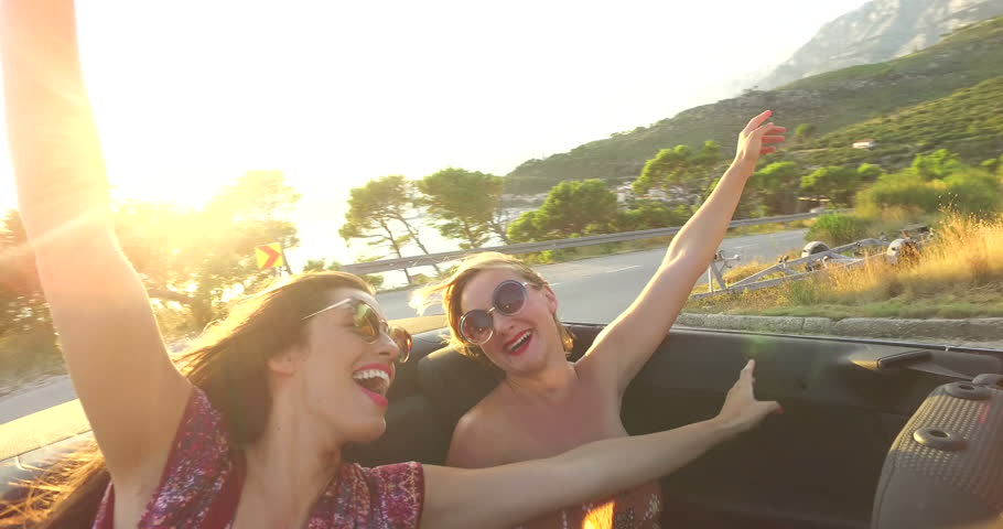 Beautiful young boho dressed women enjoying sunset while riding at the back seat of convertible car #24811643