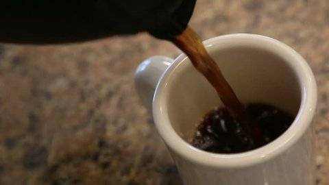 Slow Motion of Pouring Coffee Into Mug in Kitchen With Room For Text. Clip Continues as Bubbles Float and Pop.