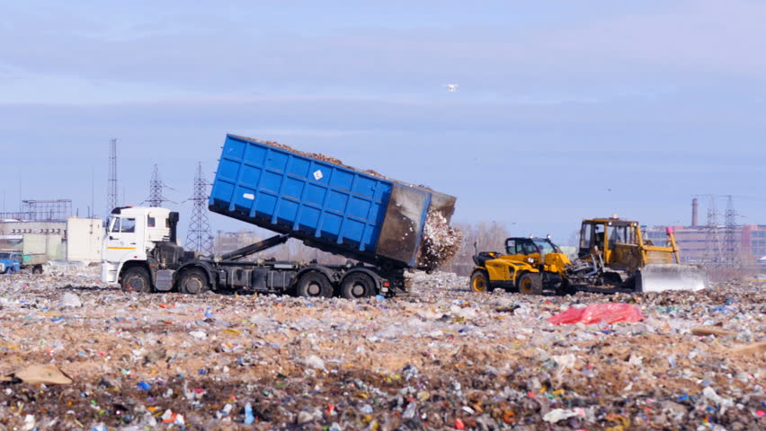 4K. Truck offloading waste into a huge landfill.