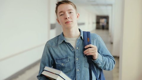 Portrait of a happy male caucasian student standing in a busy hallway with books and backpack