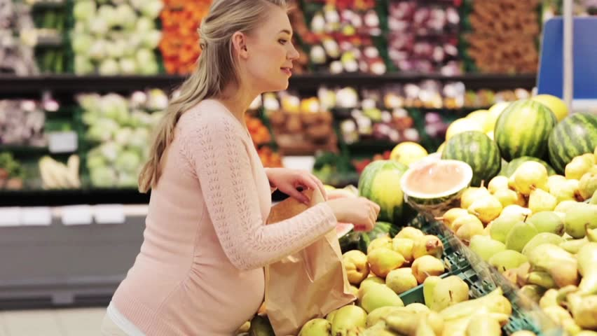 sale, shopping, food, pregnancy and people concept - happy pregnant woman buying pears and putting them into paper bag at grocery store or supermarket