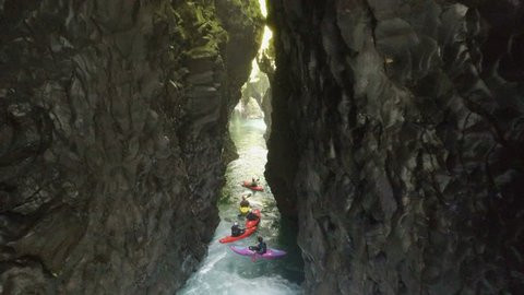 Aerial - Flying through tight canyon with kayakers paddling river - New Zealand