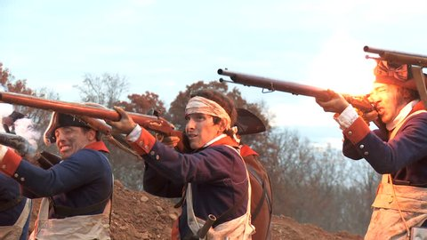 VIRGINIA - OCTOBER 2014 - Reenactment, large-scale, epic American Revolutionary War anniversary recreation - in the midst of battle.  Continental Soldiers fire on British with muskets in smoke, flag.