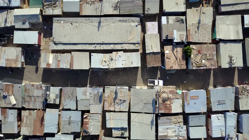 Aerial top-down view of slum a heavily populated urban informal settlement characterized by substandard housing and squalor showing people walking through streets and rusty metal home roof tops 4k