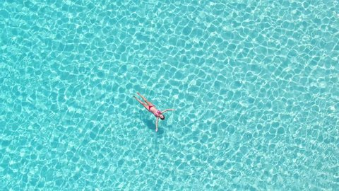 Aerial view of an attractive woman in a red bikini floating in crystal clear sea