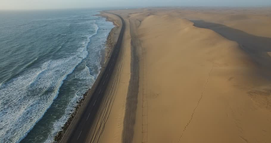 4K aerial drone view of Namibian Atlantic coastline, road along the coast from Swakopmund to Walvis Bay,  beach, surf break point, landscape with ocean background of sand dunes at Namibia's west coast