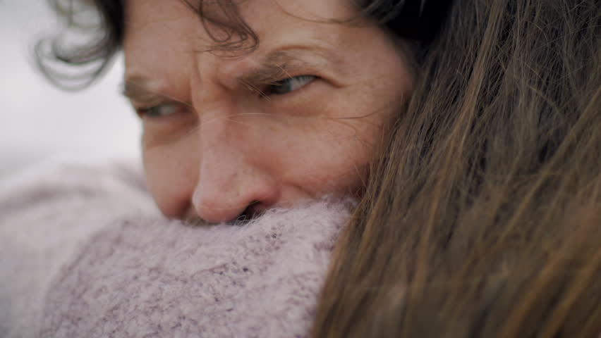 Sad man almost crying hugging and holding woman he loves closeup