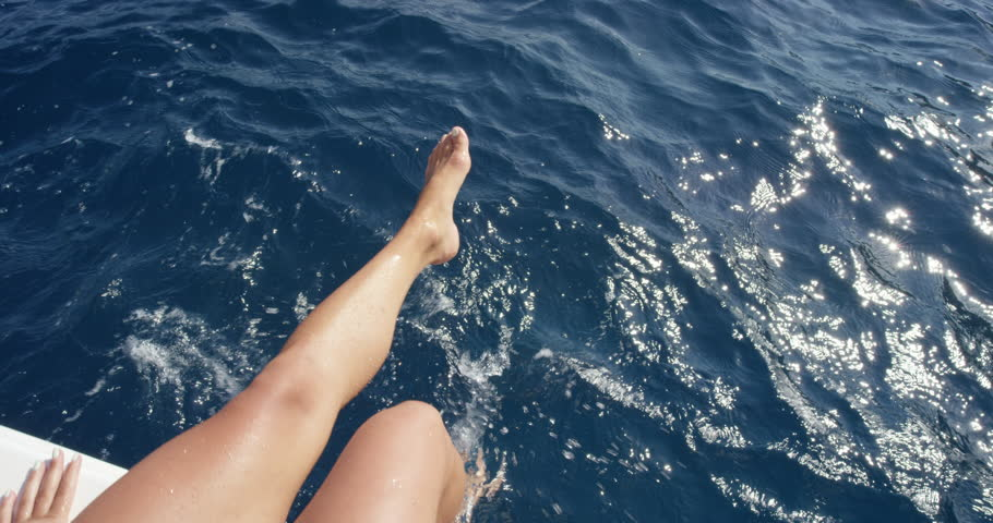 Top view female legs in water Woman splashing and playing with feet in ocean off edge of boat enjoying European summer holiday travel vacation adventure in Amalfi Coast Italy from above