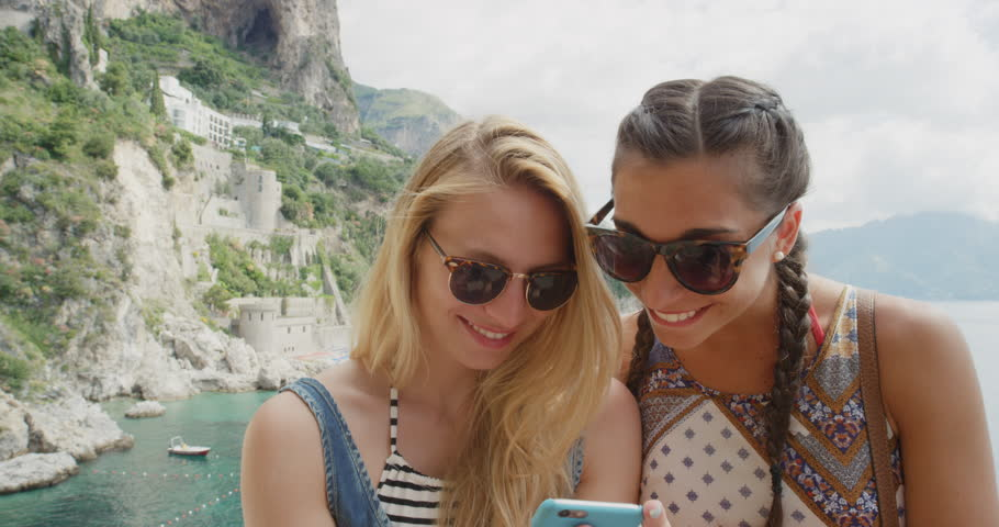 Two young women hanging out at beach using mobile phone sending text message snapchat sharing digital content on social media tourist girls enjoying summer vacation on Amalfi Coast Italy