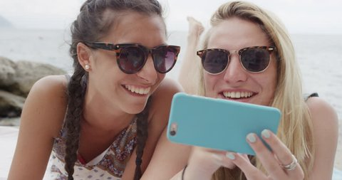 Two teenage girl friends hanging out at beach using mobile phone sending text message snap chat sharing digital content on social media enjoying summer vacation