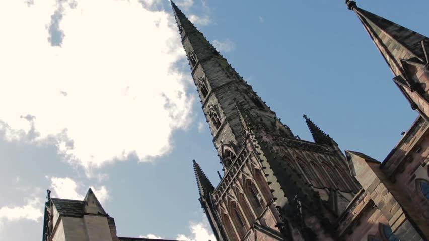 Angled shot demonstrating the Gothic Architecture of Lichfield cathedral, silhouetted against the blue sky, peppered with wisps of cloud on a glorious summers day