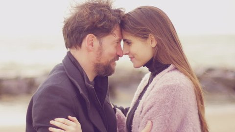 Man and woman nose to nose looking at each other in love romantic magic moment of love