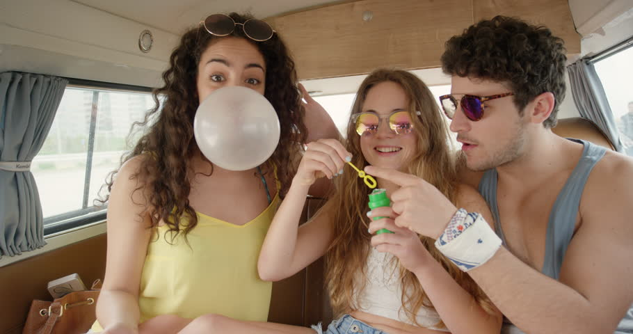 Portrait Beautiful Teenage hipster friends blowing soap bubbles at festival in camper van on road trip adventure
