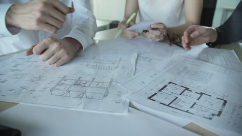 Close up hands of three workers discussing building drawings in office. Closeup shooting of arms moving pictures, watching attentively on images. design drafts for construction of large sports complex