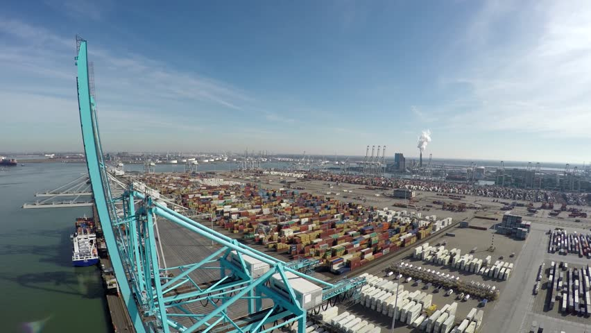 Aerial bird view flying over harbor area past blue harbour cranes for loading or unloading intermodal containers in background a container terminal with containers ready for transport blue sky 4k