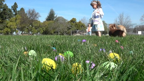 Slow motion of kids having fun gathering eggs at Easter hunt