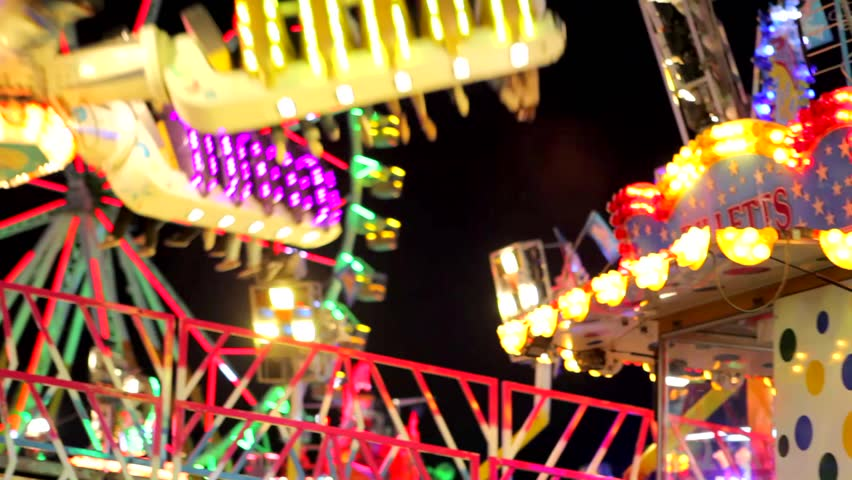 Panning view of a colorful fun fair ride at night.