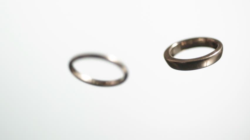 Studio shot of two wedding rings falling against white background