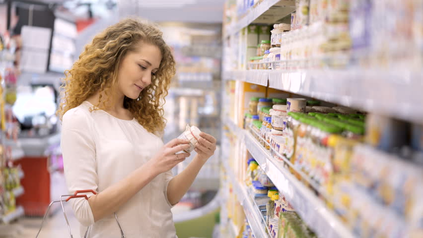 Cute 30s brunette model with long curly hair makes purchases in department store close up. Young mom selects puree, juices for child and puts baby food in basket holding hand. Consumer society concept | Shutterstock HD Video #25011083