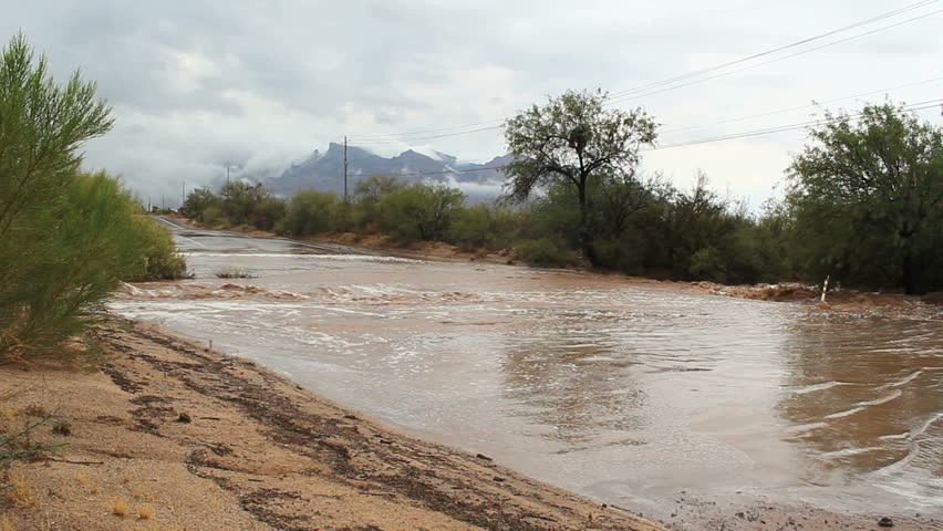 Rainwater gushes onto road from overflowing desert wash, causes flash flooding after monsoon, summer storm in Tucson, Arizona. 1080p
