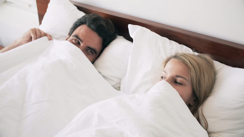 Close up of sweet couple flirting in bed - 4K stock footage clip
