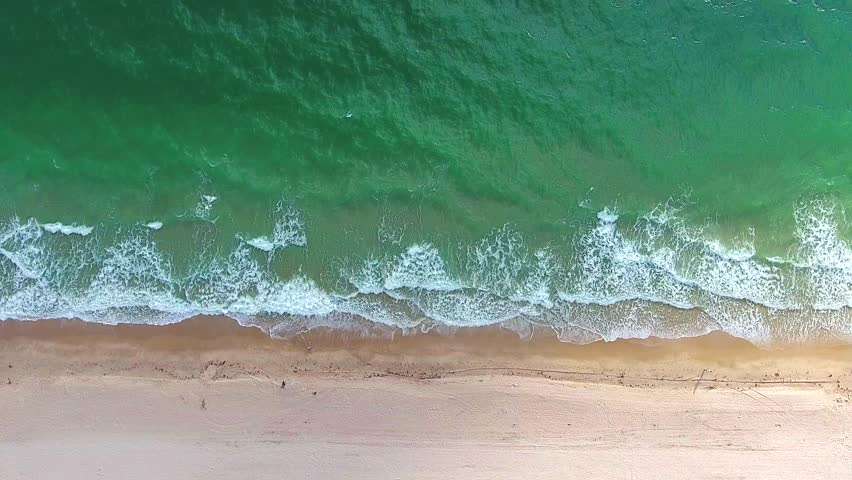 Tropical beach video loop showing seamless never ending footage with aerial bird eye view of green foaming ocean waves crushing against the coast line of Florida and overhead view of a seldom tourist #25022873