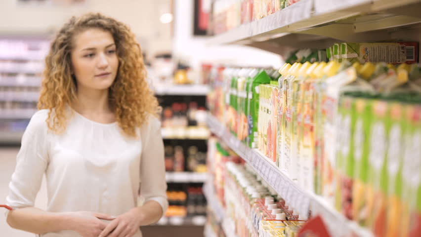 Woman chooses juice in the supermarket. Shopping in the store. Young female carefully analyzing products in a market. Shopping in Grocery Store or Supermarket | Shutterstock HD Video #25025123