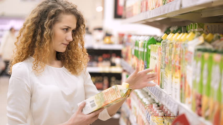 Woman chooses juice in the supermarket. Shopping in the store. Young female carefully analyzing products in a market. Shopping in Grocery Store or Supermarket