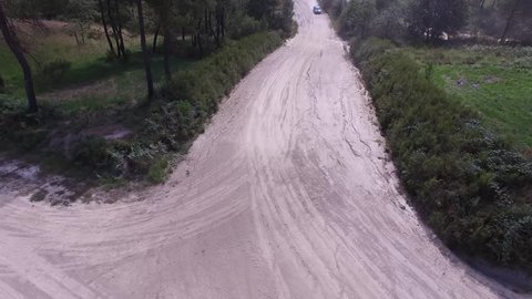 Aerial of Subaru Rally car slowing down and taking a corner
