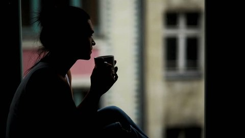 Closeup Portrait of Beautiful Woman in Front of the Window with Cup of Hot Beverage in the Morning. Silhouette of Amazing Girl that Enjoying Coffee Alone Sitting on the Windowsill.