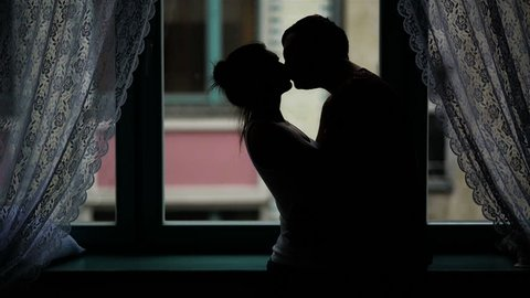 Passionate Couple is Kissing and Hugging in the Darkness. Silhouette of the Man and Woman in Love near the Window.