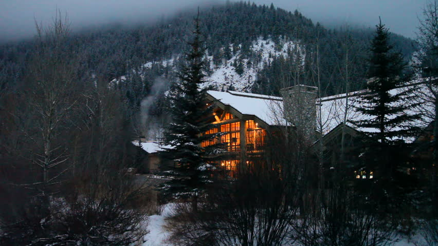 Ski resort lodge on a winter evening, illuminated by a warm glow.