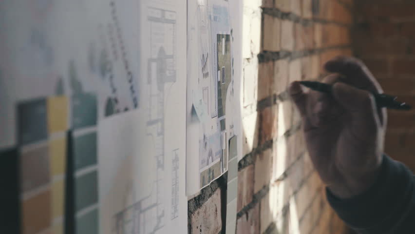 Stylish and modern cabinet in the loft style: A brick wall with notes and blueprints. Drawings and diagram of future buildings on the wall, there is blueprints and model house on the wall